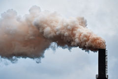 Red smoke. Industrial smokestacks with billowing red smoke being pumped into the atmosphere Royalty Free Stock Image