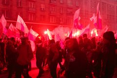 Independence Day March in Warsaw Poland Marred by Violence and Controversy. Red smoke fills the air as protesters wave flares and flags at the annual Polish Royalty Free Stock Photo