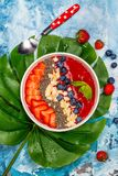 Red smoothie bowl. With strawberry, blueberry and chia seeds on blue ocean background with monstera leaf. Copy space royalty free stock photography