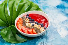 Red smoothie bowl. With strawberry, blueberry and chia seeds on blue ocean background with monstera leaf. Copy space royalty free stock photo