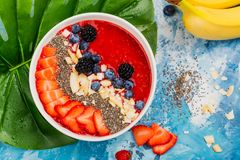 Red smoothie bowl. With strawberry, blueberry and chia seeds on blue ocean background with monstera leaf. Copy space royalty free stock photos