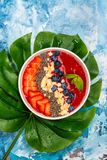 Red smoothie bowl. With strawberry, blueberry and chia seeds on blue ocean background with monstera leaf. Copy space stock image