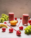 Red smoothie drink in glass with straw and fruits berries ingredients on white wooden background, top view  strawberries, whit Royalty Free Stock Photography