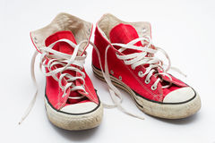 Red sneakers. Red used sneakers on a white background Stock Images
