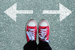 Red sneakers with arrows in two directions Royalty Free Stock Photos