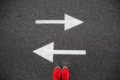 Red sneakers on the asphalt road with drawn arrows pointing to two directions Royalty Free Stock Photos