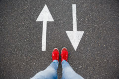 Red sneakers on the asphalt road with drawn arrows pointing to two directions Royalty Free Stock Photography