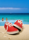 Red sneakers at the beach. Red sneakers on beautiful beach. Two persons walking into turquoise water. Shallow depth of field, focus on the sneakers. Digital Stock Photo