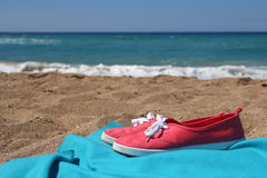Red sneakers and blue blanket on beautiful beach Stock Images