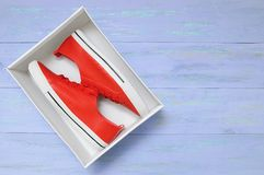 Red sneakers in a box. On a blue wooden background royalty free stock photography