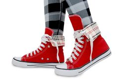 Red sneakers, checkered leggings. Royalty Free Stock Images