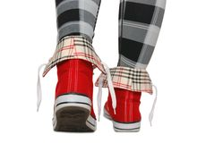 Red sneakers, checkered leggings. Stock Image