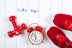 Red sneakers, clock and dumbbells on wooden backgroyund. Just run. Stock Photos