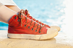 Red sneakers on girl and seascape as background Royalty Free Stock Photo