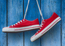 Free Red Sneakers Hanging On A Wooden Blue Background Royalty Free Stock Photo - 72856315