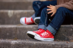 Red sneakers on a kids feet, sitting on stairs Royalty Free Stock Photos