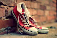 Red sneakers leaning against a brick wall with retro effect Royalty Free Stock Image