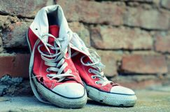 Red sneakers leaning against a brick wall with retro effect Royalty Free Stock Photography