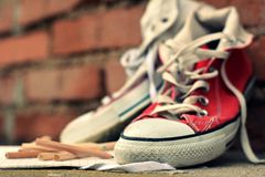 Red sneakers and pastels leaning against a brick wall Stock Photos