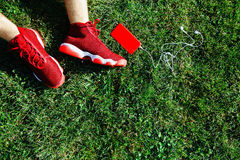 Red sneakers, phone and walkmans on pitch Royalty Free Stock Photos