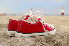 Red sneakers on sandy beach. Red sneakers sitting on sandy beach on sunny day Royalty Free Stock Images