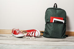 Red sneakers with school bag on wooden background Royalty Free Stock Photo