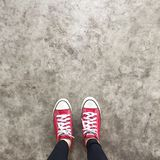 Red Sneakers Shoes Walking On Dirty Concrete Top View , Canvas Shoes Walking On Concrete Royalty Free Stock Photos