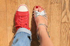 Red sneakers and silver high heels shoes Royalty Free Stock Photography