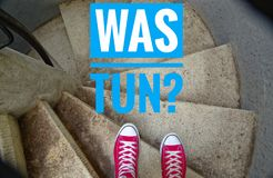Red sneakers on spiral staircase when going downhill with inscription in german Was tun? in english What to do?.  royalty free stock images
