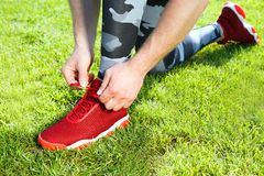 Red sneakers. Sport concept. Man tightening lacings of red sneakers, one leg ahead. Without head. Green grass, outdoors, stadium, only legs Stock Images