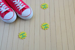 Red sneakers with spring signs on the wooden background Royalty Free Stock Images