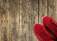 Red sneakers on wooden deck. Red sneakers in the right side on wooden deck stock photos