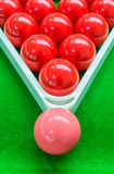 Red snooker balls set in triangle frame and one pink ball on top Stock Images