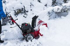 Red snow blower cleaning driveway Royalty Free Stock Photos