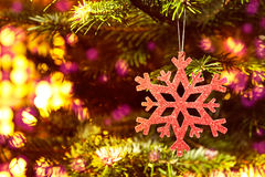 Red snow flake in a christmas tree Royalty Free Stock Photography