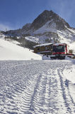 Red snow groomer in the mountain stock image