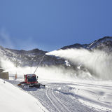 Red snow groomer and snow canon in the mountain Royalty Free Stock Images
