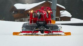 A red snowcat or snow groomer in action stock image