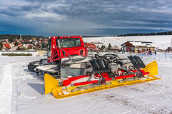 Red snow-grooming machine on snow Stock Photo