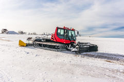 Red snow-grooming machine on snow Stock Photos