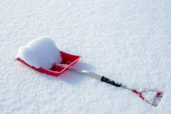 Red snow shovel lying in the snow Royalty Free Stock Photos