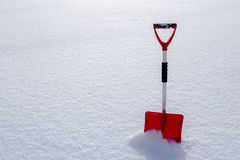 Red snow shovel standing in the snow Stock Photos