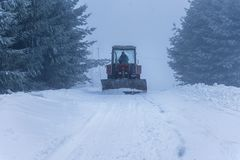 Red snowblower grader clears snow covered ski resort road. Stock Photo