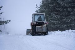 Red snowblower grader clears snow covered ski resort road. Stock Photos
