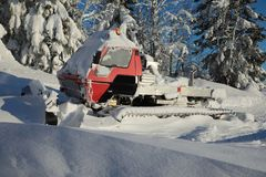 Red snowcat covered in snow on mountains Royalty Free Stock Images