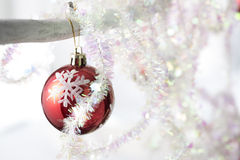 Red snowflake bauble with silver tinsel Stock Image