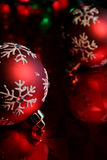 Red Snowflake Baubles Upclose. Two red christmas baubles illuminated on glossy red paper Stock Photography
