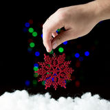 Red snowflake in the hand  on the black background. With colorful bokeh Royalty Free Stock Images