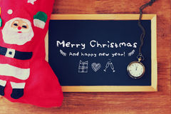 Red sock and blackboard with merry christmas greeting and icons. christmas card concept Stock Photography