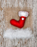 Red sock with burlap textile and snow Royalty Free Stock Photos
